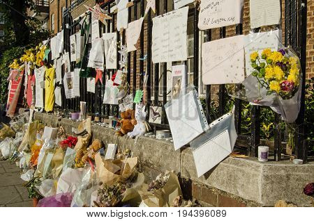 LONDON UK - JULY 5 2017: Railings close to Grenfell Tower covered in memorials to those killed and missing. At least 80 people are thought to have died in the fire in the council tower block of flats in Kensington London.