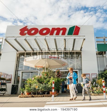 FRANKFURT GERMANY - JUN 30 2017: Mother and child walking to the entrance of TOOM the German DIY-store chain offering home improvement and do-it-yourself goods - customers buying goods selecting the best tools