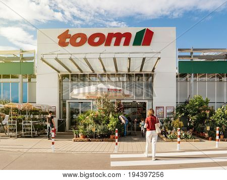 FRANKFURT GERMANY - JUN 30 2017: Woman walking to the entrance of TOOM Baumarkt the German DIY-store chain offering home improvement and do-it-yourself goods - customers buying goods selecting the best tools