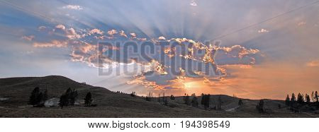 Sunbeams and sunrays through sunset clouds in the Hayden Valley in Yellowstone National Park in Wyoming US of A