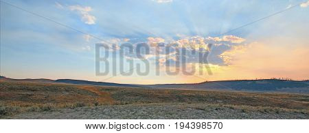 Sunbeams and sunrays shining through sunset clouds in the Hayden Valley in Yellowstone National Park in Wyoming USA poster