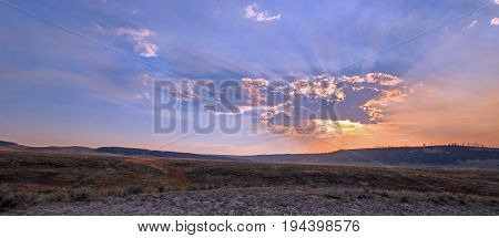 Sunbeams shining through sunset clouds in the Hayden Valley in Yellowstone National Park in Wyoming USA