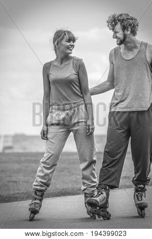 Woman And Man Couple Rollerskates Outdoor