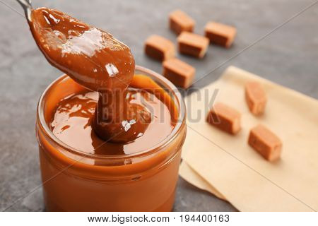 Glass jar with tasty caramel sauce and spoon on table