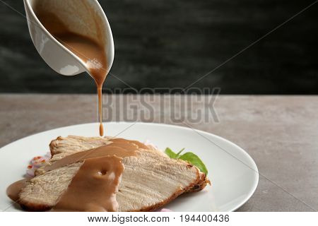 Pouring tasty turkey gravy onto sliced meat on plate against dark background