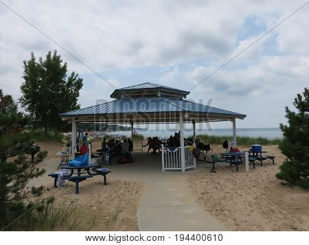 Pavilion with people enjoying the day despite weather front moving thru at Silver Beach County Park in St. Joseph, Michigan
