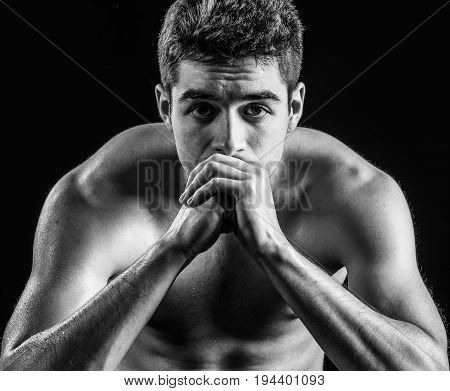 Portrait of man staring at camera with hands folded in front of him