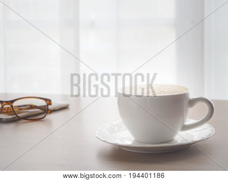 wood table with hot coffee cup and modern eyeglasses on blurry white drape background.