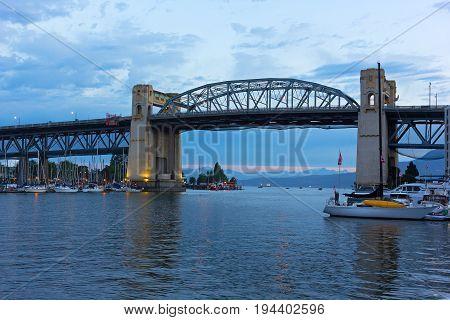 Burrard Bridge at dawn in Vancouver British Columbia Canada. Steel truss bridge over False Creek with imposing concrete towers before sunrise.