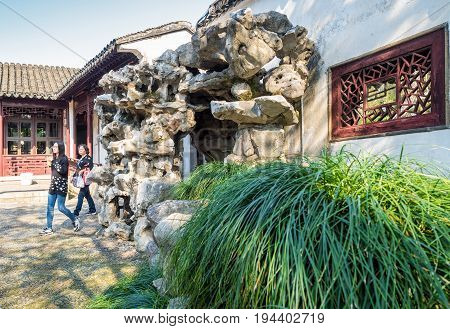 Suzhou, China - Nov 5, 2016: Master of Nets Garden (Wang Shi Yuan) - Wall entrance to a residential building that is framed by ornate rock formation.