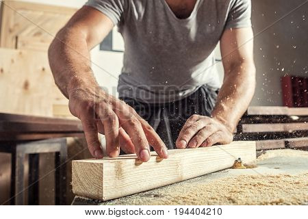 A young male carpenter builder in a gray T-shirt and working overall equals a wooden bar with a milling machine in the workshop in the background wooden boards