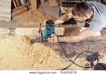 A young brunette man in safety glasses and a gray T-shirt is working a wooden board with a milling machine in the workshop around a lot of wooden sawdust and wooden boards