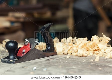 A black jack plane is on a wooden table next to a wooden sawdust in the workshop