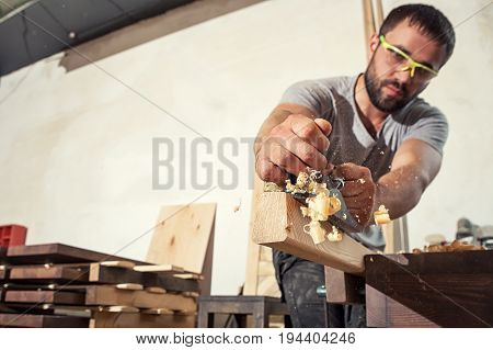 A young brunette man builder in green glasses and a gray T-shirt handles a wooden bar with a black jack plane in the workshop in the background a lot of wooden boards