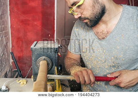 A young brunette man builder wearing green protective goggles a gray T-shirt and with a beard working on a wooden workpiece on a lathe in the workshop...