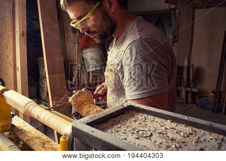 A handsome brunette man builder carpenter makes a wooden product on a lathe in the workshop around a lot of sawdust