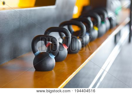 Black metal weights kettlebell in one row in the gym