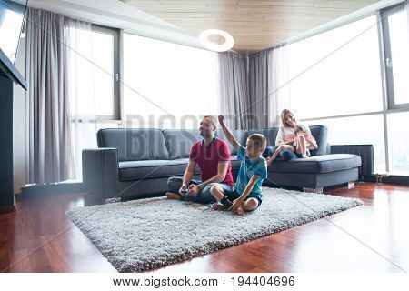 Happy family. Father, mother and children playing a video game Father and son playing video games together on the floor