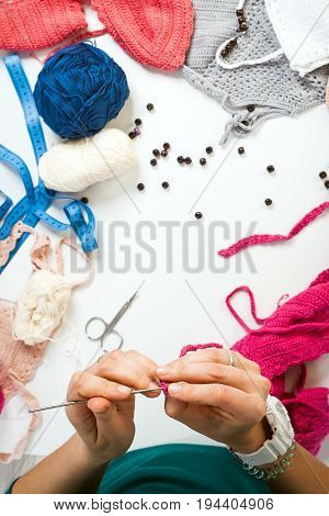 A young woman knits a woolen thread with a woolen thread female top view white woolen threads are laid out on a white table: white blue gray and vaped tops