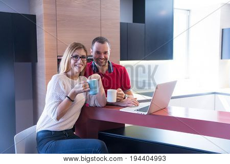 Young couple drinking coffee and using laptop computer at luxury home together, looking at screen, smiling.