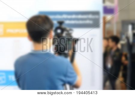 Blurred image of young camera man filming an event with a video camera.