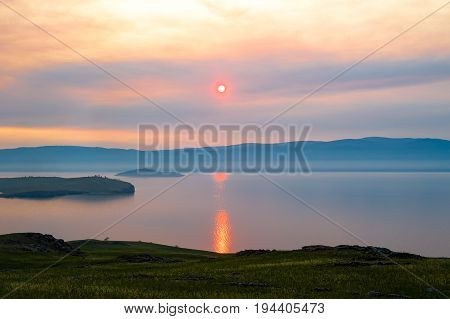 View of the sunset from the island of Olkhon. Cape Elgay, Zamogoi Island and the western shore of Lake Baikal are seen. Siberia, Russia