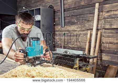 A man with dark hair and a beard in safety glasses and a gray T-shirt is holding a milling machine and handles a wooden board in the workshop at the back of the board there are many wooden boards