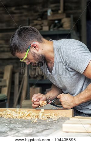 A young man with a beard  by profession the carpenter holds a black jack plane in his hands and equals a wooden board in the background a lot of wooden boards and equipment