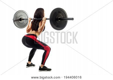 Young sportive woman fitness model brunette makes a squat with a barbell on white isolated background Semi-squat position