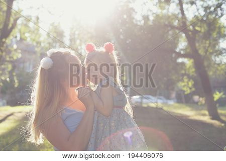 Family values. Mother and daughter. Mother holding her baby in her arms. Same dresses and hairstyles. Backlight of the setting sun. Mother kisses the daughter. Family look