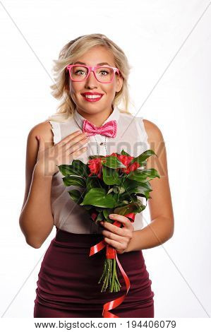 Pretty young teacher with a bouquet of flowers. A gift for the teacher's day. The girl is surprised and happy about the gift. She is wearing a blouse a bow tie and glasses. Back to school.