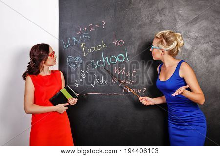 Two young attractive female students at the school board. They are looking at the board. One girl holds a notebook another pointer. Back to school. Best friends forever. Education.