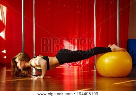 Pole dancer makes a stretch on the fitball before classes. Flexibility and plasticity. Young attractive sexy girl. She's wringing out.