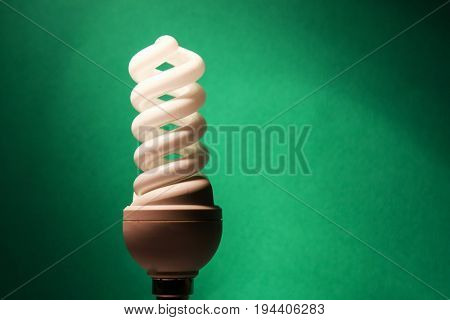 Light bulb glowing on green background