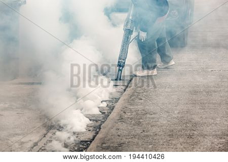 Worker fogging street drain with insecticides to kill aedes mosquito breeding ground, carrier of dengue and Zika virus .