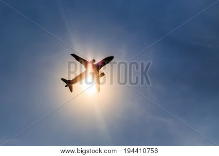 Silhouette airplane taking off over blue sky at sun background .