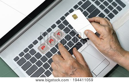 Elderly person using credit card for online shopping .