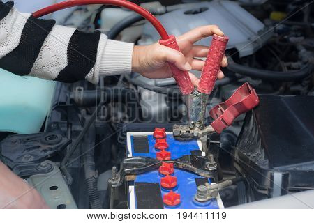 woman hand hold jumper cables to car battery .