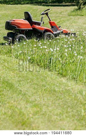 Red Lawn Mower At Rest On A Farm Field Against Green Grass Background