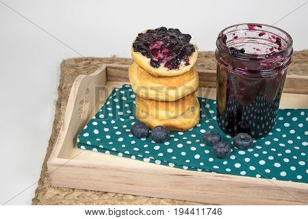 blueberry jam and stack of bread rolls on polka dot cloth napkin and wooden serving tray