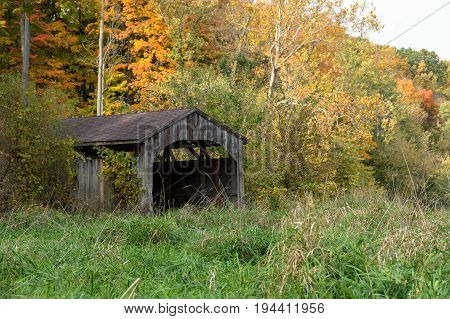 old wooden covered bridge in autumn woods