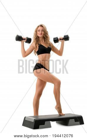 Image of curly athlete posing with dumbbells and stepper