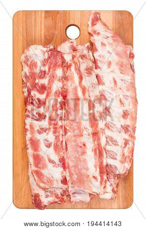 Raw pork ribs on wooden cutting Board closeup. White background, top view