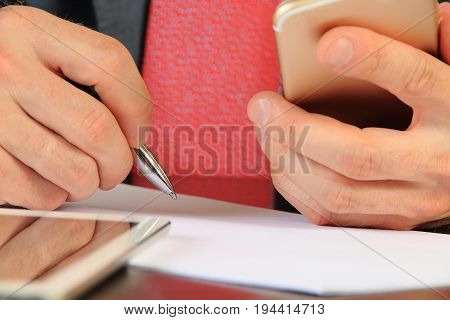 Businessman hands with smartphone and pen close-up. Businessman looking for partners online. Searching business partners concept.