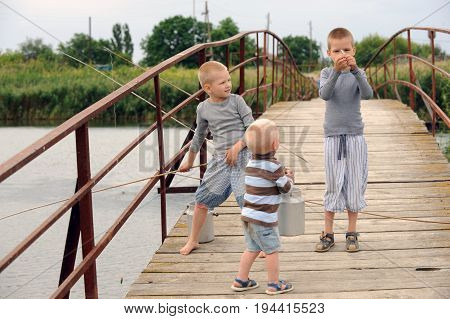 Three brothers came to the bridge in the village across the river to fish but instead ran along the bridge from the excess of feelings with a tourist aluminum kettle and small fish cans