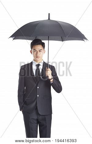 young asian business man in formal wear holding an umbrella looking at camera with one hand in pocket isolated on white background.