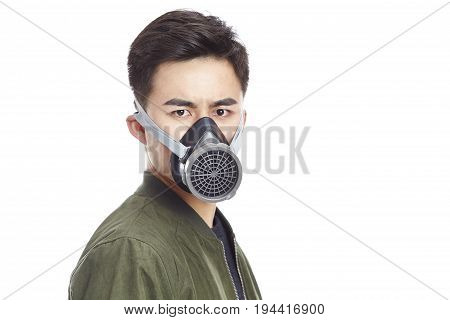 young asian man wearing gas mask staring at camera isolated on white background.