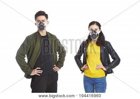 young asian man and woman wearing gas mask staring at camera with arms akimbo isolated on white background.