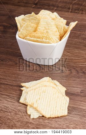 Salted Potato Crisps In White Glass Bowl On Board, Concept Of Unhealthy Food