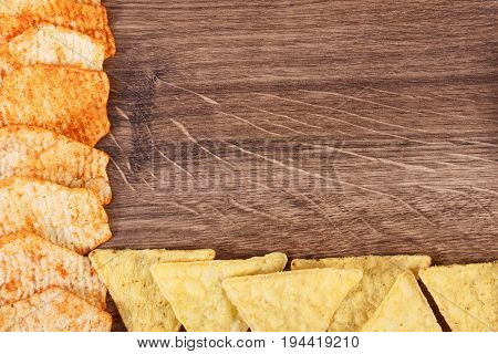 Frame Of Salty Crisps, Concept Of Unhealthy Food, Copy Space For Text On Rustic Board